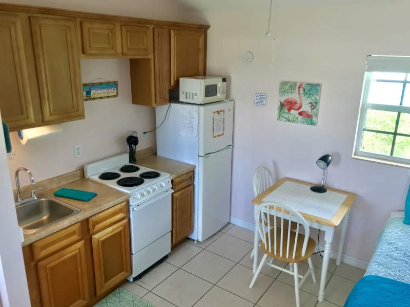 Kitchenette with small table, sink, counterspace, stove, refrigerator, and microwave.