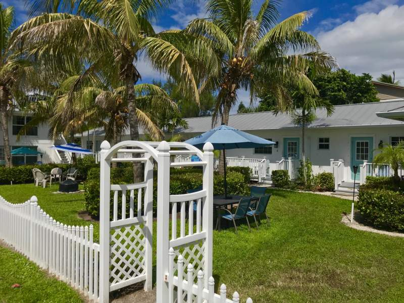 Exterior of bungalows, courtyard, tables, chairs, umbrellas, green grass, palm trees and white picket fence.
