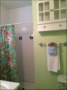 Partial view of white sink and shower, tropical curtain, light green walls, small cabinet, towel bar