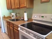 galley style kitchen, oak cabinets, flat top stove, dishwasher, coffee maker