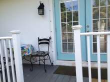 Deck with white railing, small table with chairs, double french doors into bungalow