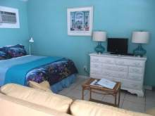 Blue interior, double bed, couch, dresser, lamp, coffee table
