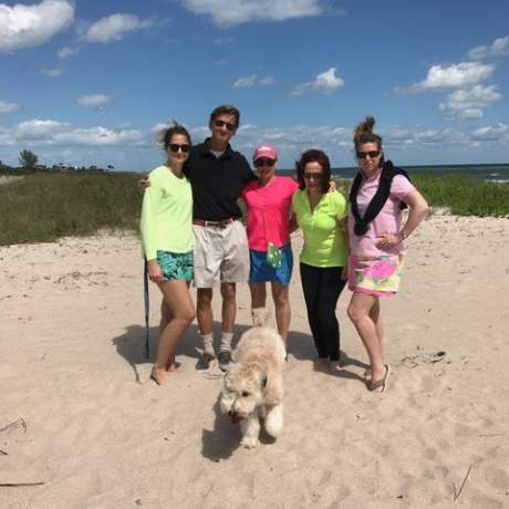 Family posing on the beach with dog