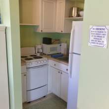 Green kitchen with white cabinets, sink, microwave, refrigerator