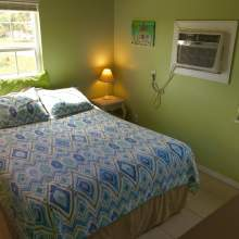 Green wall, double bed with blue and green bedding, lamp, window, wall air conditioning unit