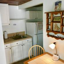 White kitchen cabinets, sink, refrigerator. Partial view of two person table