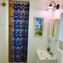 Bathroom shower with blue and white curtain, white walls, sink, lighthouse image