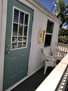 Outdoor deck, white exterior, blue door, two chairs, deck railing
