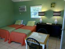 Two twin beds, orange bed spreads, dresser, lamps, wall air conditioning unit, two person table