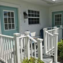 Front door of bungalow with deck, railing and chair