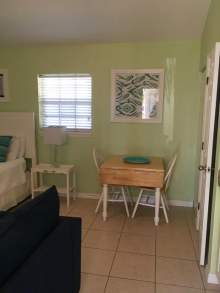 Light green walls, two person table, partial images of bed and couch