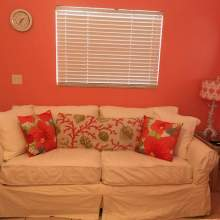 Window, sofa with white fabric, decorative pillows, coral colored walls