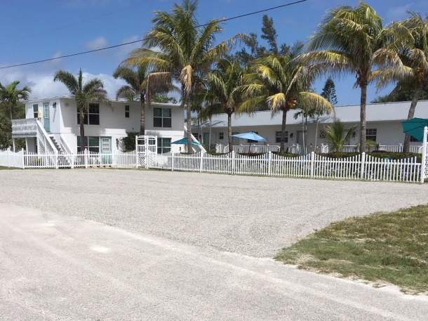 Seahorse Beach Bungalows parking lot, two story apartment style building with palm trees, picket fence