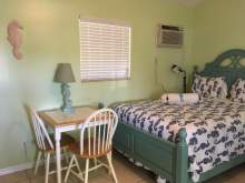 Light green interior, window with blinds, air conditioning unit, two person table, partial image of double bed