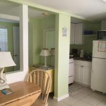 Partial image of kitchen, two person table, half wall enclosing bedroom