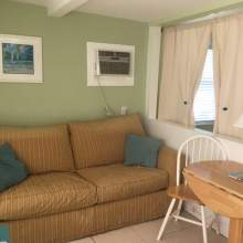 Tan sofa next to half wall. Decorative pictures, two person table