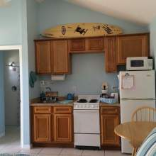 Oak kitchen cabinets, small stove, sink, microwave, refrigerator, decorative surf board