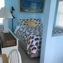 Tropical fish bedding on double bed, dresser, half wall enclosing bedroom.
