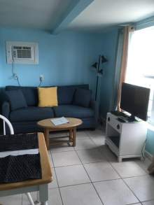 Light blue walls, dark blue sofa, coffee table, television on tv stand, two person table. Air conditioning unit in wall