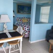 Blue interior, two person table near half wall that encloses bedroom