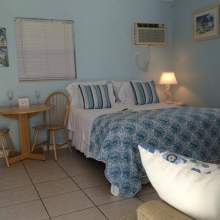 Blue and white bedding on double bed, air conditioning wall unit, window with blinds, two person table