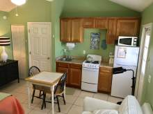 Light green kitchenette with oak cabinets, small stove, microwave, refrigerator, two person table, partial image of couch and bed