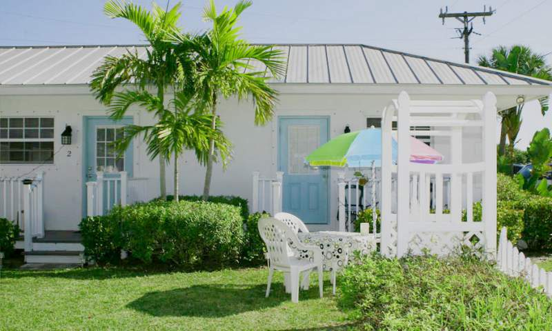 Exterior of bungalow, white building, metal roof, blue doors, palm trees, table, chairs and umbrella, trellis